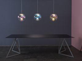 3 pendant OLED luminaires called IRIS above a steel table