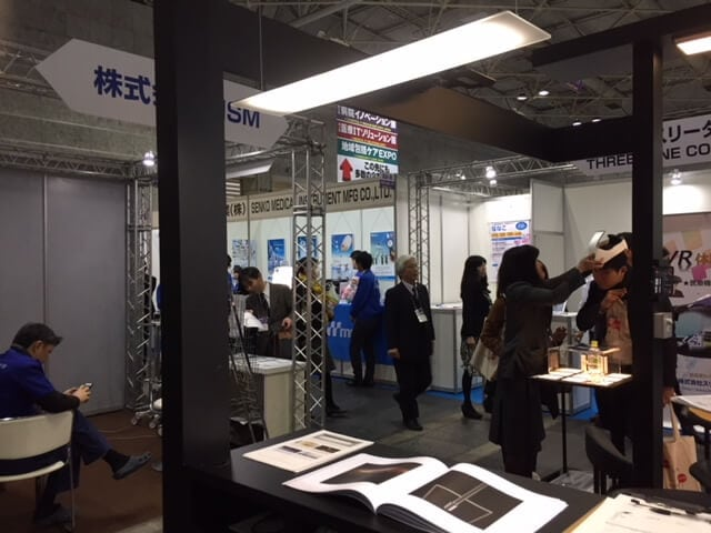 crowded Taiyo booth at Medical Japan showing OLED fixtures