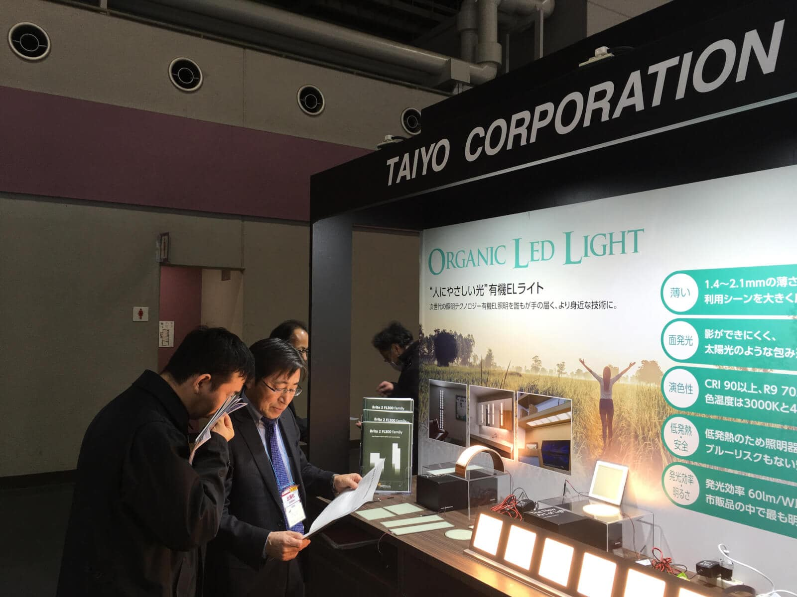 interested visitors at Taiyo booth at Medical Japan reading about OLED lighting