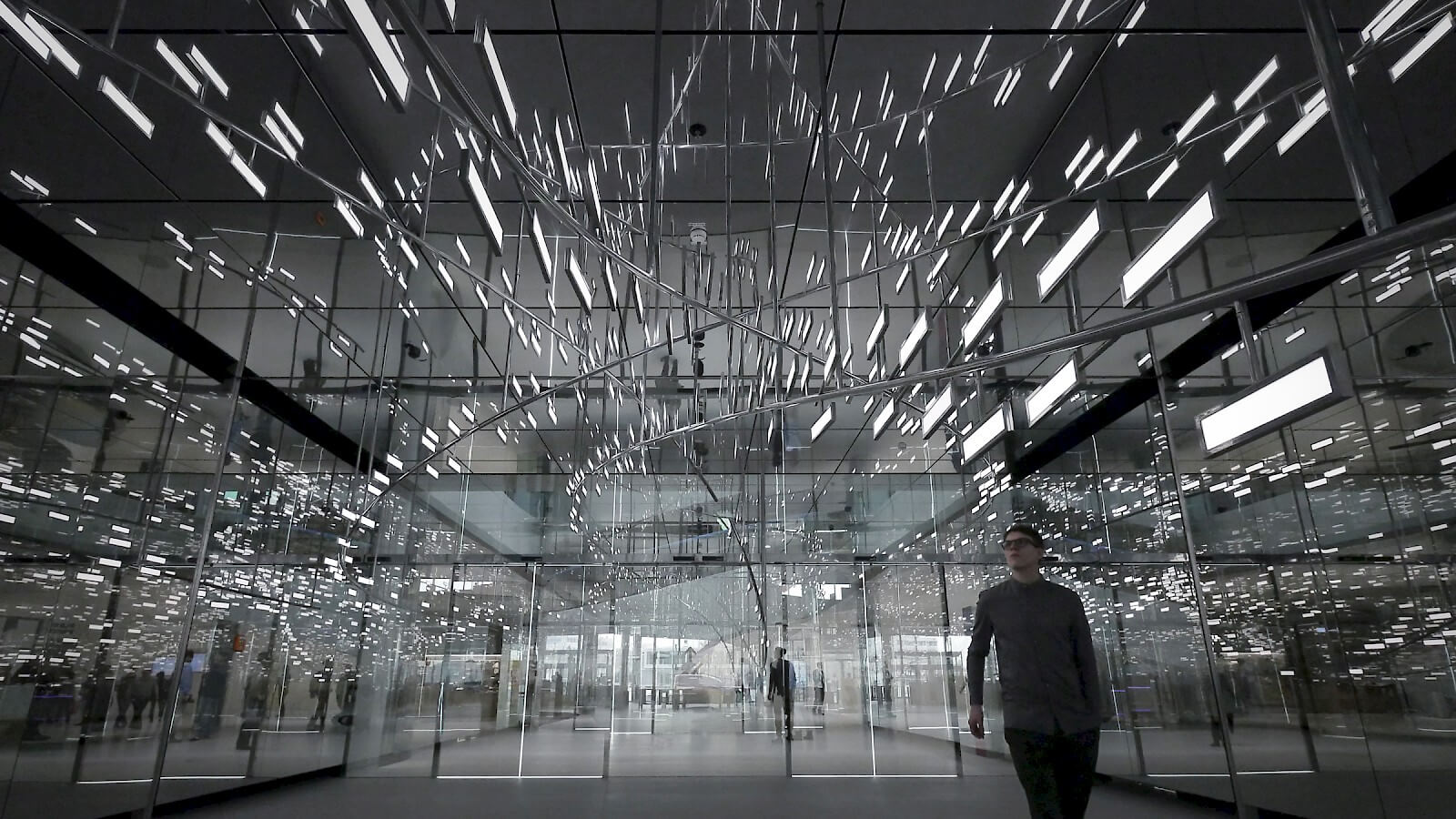 Man goes through the room with OLED lighting installation Light Cloud