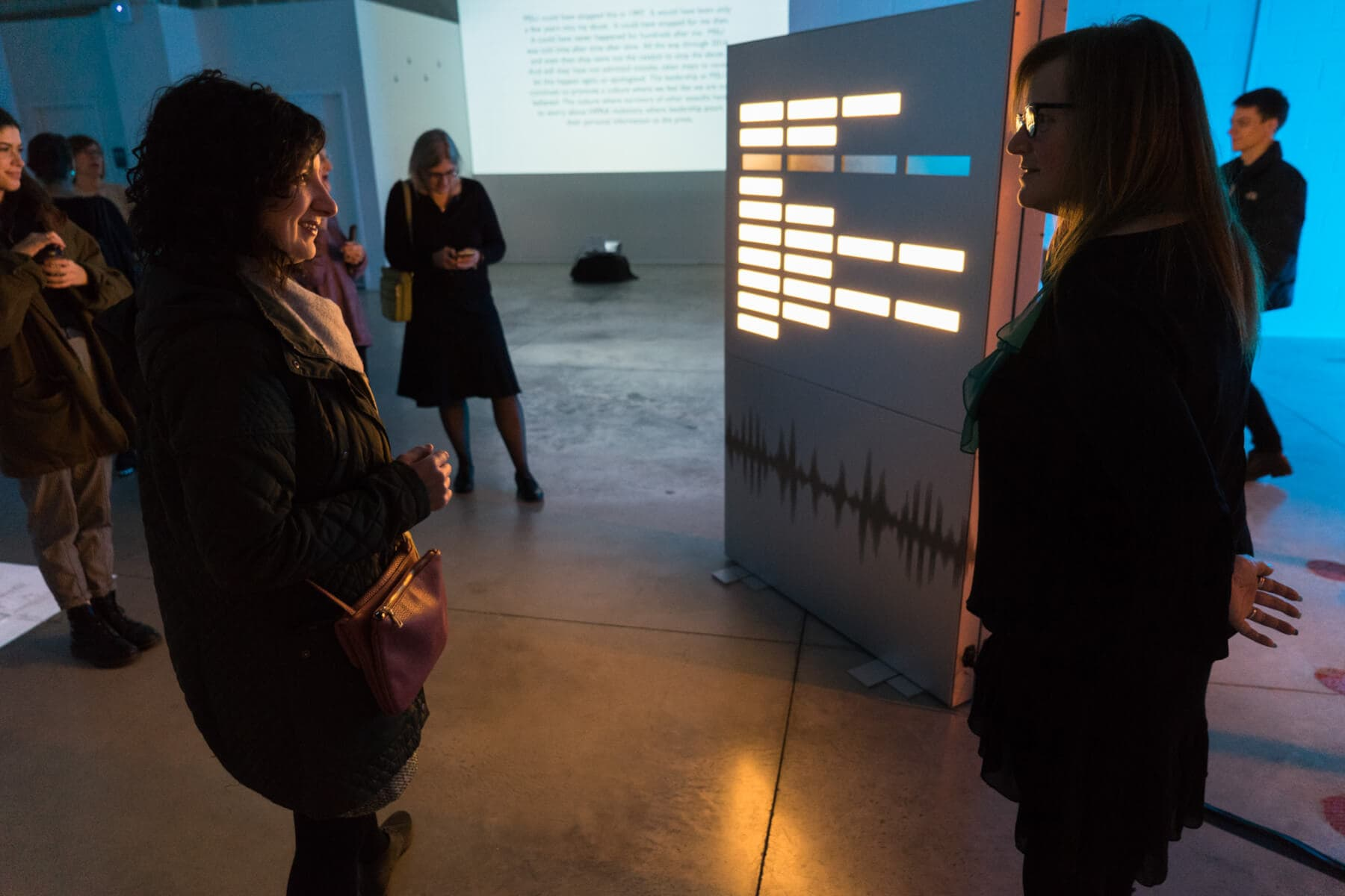 Nancy Dejoy talks to a visitor in front of the poem Illuminating Survivor Voices